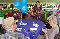 Ken and Dot Parker enjoy their strawberry sundaes on the Taylor Home front lawn while being serenaded by Cindi Meehan during the Strawberry Festival Thursday afternoon.  (Karen Bobotas/for the Laconia Daily Sun)