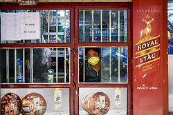 A shop owner peeks outside before opening her liquor store at a liquor joint in south Kolkata.Goverment ordered to open liquor shop amidst 14 days of extended lockdown in India. Guidelines were put forth and social distancing protocols were ordered to be followed at any cost during working hour of the liquor shop in the country. Photo by Debarchan Chatterjee/ABACAPRESS.COM