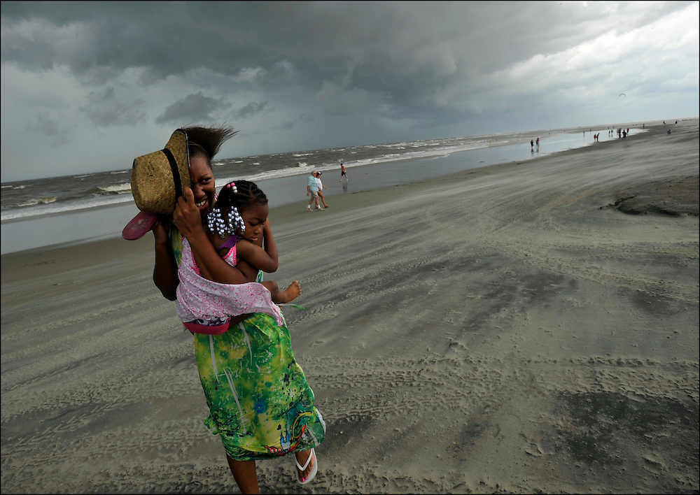 Kia Head along carries Christian Searcy in her arms while protecting their faces from wind and sand blown in from an outer band from Hurricane Irene in Tybee Island, Ga., Friday, Aug. 26, 2011. Hurricane Irene is expected to pass off shore of coastal Georgia but officals are still banning swimmers for the water due to high winds and rough seas.  (AP Photo/Stephen Morton)