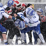 Jay Harrison, Darien, is tackled by the New Canaan defense during the New Canaan Rams Vs Darien Blue Wave, CIAC Football Championship Class L Final at Boyle Stadium, Stamford. The New Canaan Rams won the match in snowy conditions 44-12. Stamford,  Connecticut, USA. 14th December 2013. Photo Tim Clayton