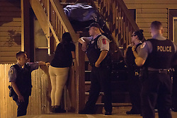 August 6, 2017 - Chicago, IL, USA - The mother of 14-year-old Damien Santoyo, who was shot to death on the porch of a residence, looks through the stairway at her son's body as Chicago police stand nearby in the 1700 block of South Newberry Avenue Sunday, August 6, 2017, in the Pilsen neighborhood of Chicago. Occupants in a passing vehicle opened fire and shot the boy in the head as he stood on the porch with two other people. (Credit Image: © Erin Hooley/TNS via ZUMA Wire)
