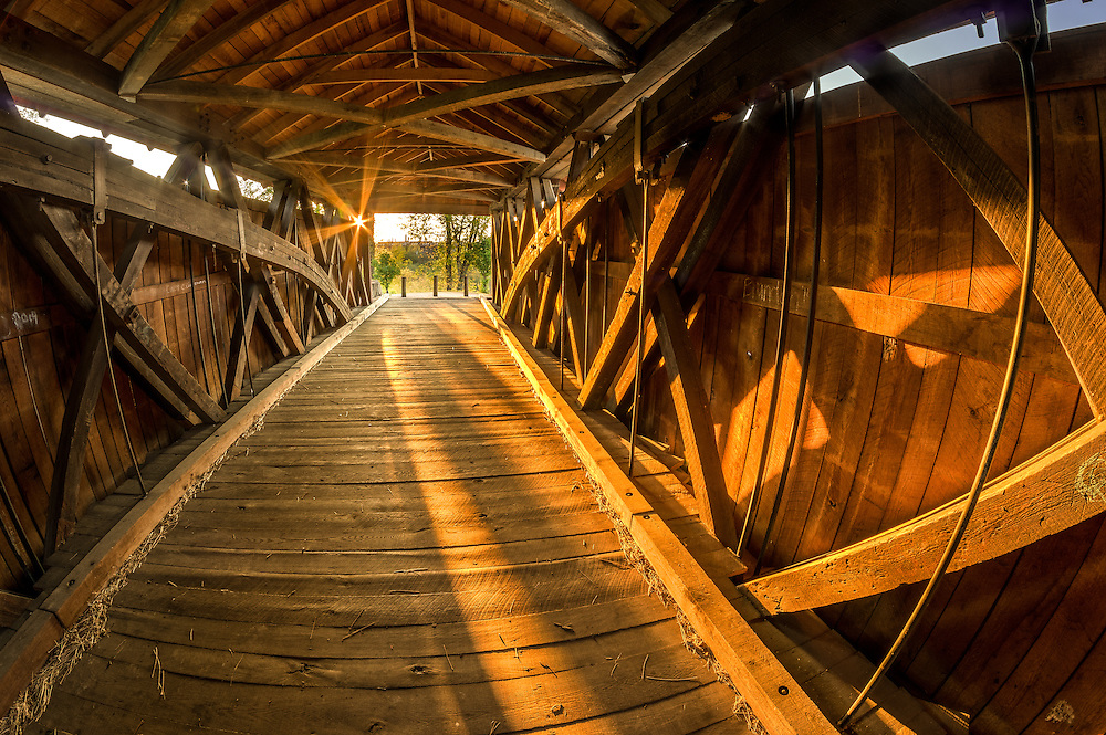Setting sun through the wooden frame of the covered bridge in Milton, West Virginia.