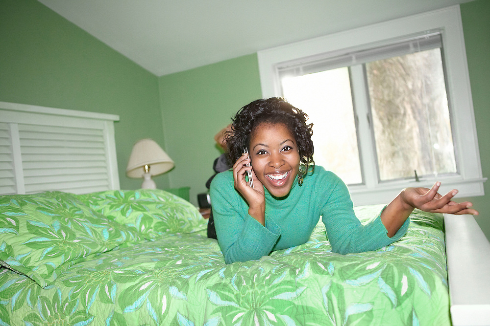 Lifestyle image of African American girl with cellphone talking on bed