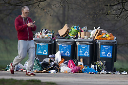 © Licensed to London News Pictures. 31/03/2021. London, UK. A man walks past overflowing bins in Greenwich Park after hundreds of people visited the park to enjoy sunny weather and take advantage of new lockdown rules that allow groups of six to meet outside. Photo credit: George Cracknell Wright/LNP