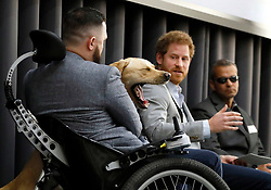 Prince Harry leads a panel discussion with former members of the UK and US Armed Forces, Ivan Castro (right), and Philip Eaglesham (left), with his Assistance Dog Cooper, during the Veterans' Mental Health Conference at the KingÕs Building in the Quad, KingÕs College London.