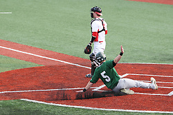 21 April 2015:  Expecting a throw that doesn't arrive, Danny Jackson stands in front of the plate as Tim Coonan slides in for a run during an NCAA Inter-Division Baseball game between the Illinois Wesleyan Titans and the Illinois State Redbirds in Duffy Bass Field, Normal IL
