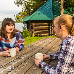 Two women drink coffee outside their cabin next to Long Pond at the Appalachian Mountain Club's Gorman Chairback Lodge.