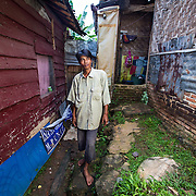 CAPTION: Mr Firdauli stands outside his house. Being so close to the river, it's highly susceptible to flooding. LOCATION: Langkapura Village, Bandar Lampung, Indonesia. INDIVIDUAL(S) PHOTOGRAPHED: Mr Firdauli.