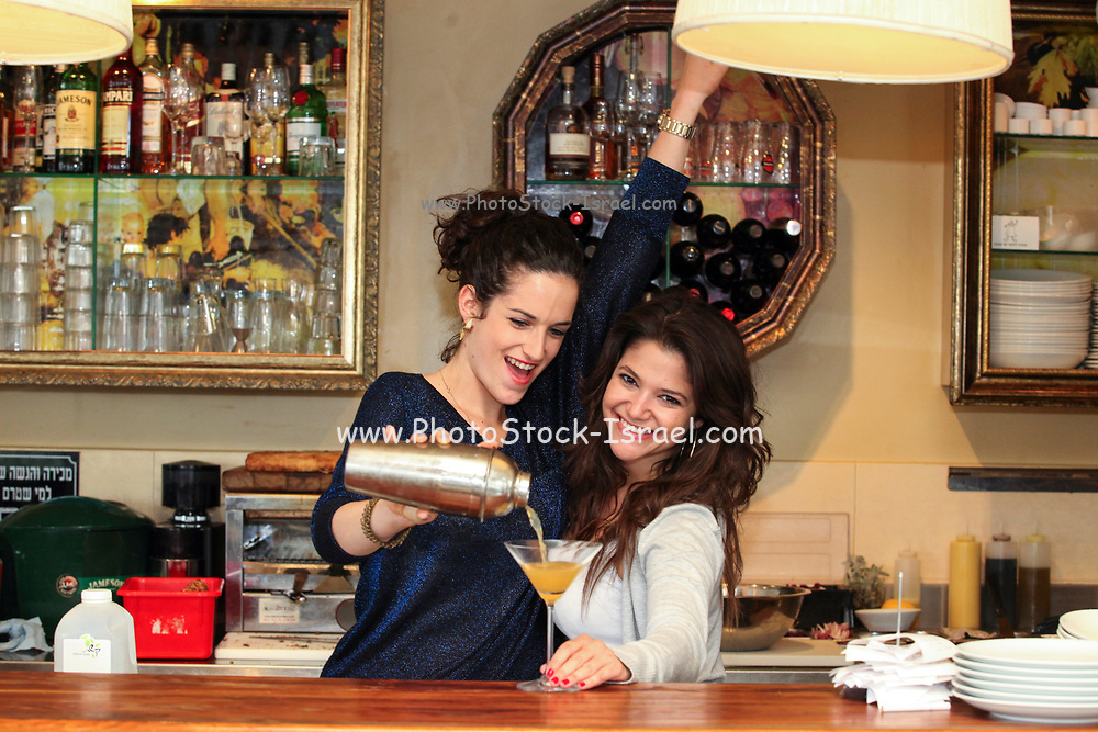 Two young woman prepare a cocktail