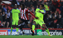 Brentford's Romaine Sawyers, left battles for possession of the ball with Derby County's Tom Huddlestone`, right