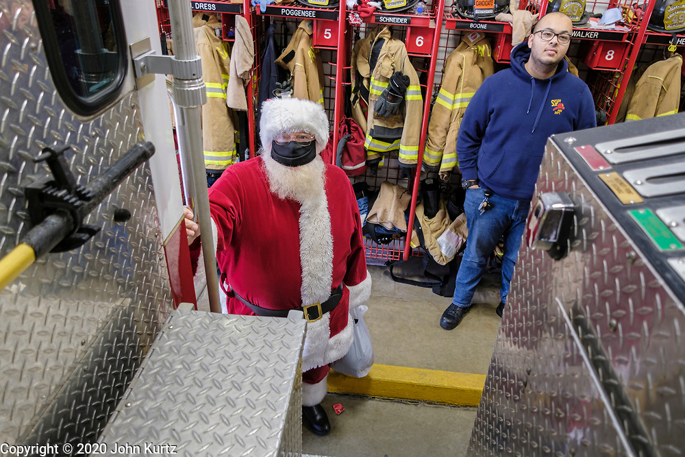 19 DECEMBER 2020 - SAYLOR TOWNSHIP, IOWA: SANTA CLAUS and a Saylor Township firefighter check out Santa's seat on top of a firetruck before Santa was driven through town. The Saylor Township Fire Department welcomed Santa Claus to the township on the north edge of Des Moines by showing him around town a fire engine. The event was organized by the Fire Deparment for the town's youngsters who won't be able to see Santa this year because of the Coronavirus pandemic.     PHOTO BY JACK KURTZ