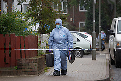 © Licensed to London News Pictures. 19/09/2013. London, UK. A police forensics officer carries equipment at the scene of a shooting on Coppock Close in Battersea London today (19/09/2013). Taking place at around 8pm last night a 19 year old male was pronounced dead at around 9pm. Photo credit: Matt Cetti-Roberts/LNP