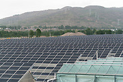 Huge field of greenhouses for growing vegetable produce, each one covered wiuth solar panels. Qinghai province near to Xining city, China