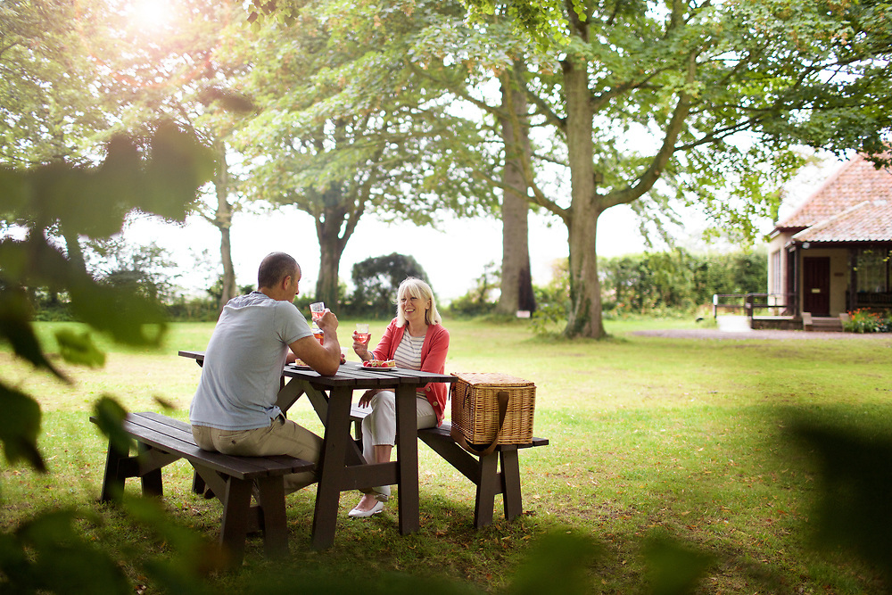 Man and woman enjoying a picnic and socialising in the garden at the Museum and Heritage site La Hougue Bie in Jersey, CI