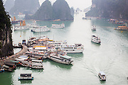03 APRIL 2012 - HA LONG, VIETNAM:  Tourist cruise boats tie up at Hang Sung Sot Cave in Ha Long Bay. In 1994 UNESCO declared 174 square miles of Ha Long Bay a World Heritage Site. There are nearly 2000 distinct rock islands in the bay, which for centuries has been the home to isolated fishing villages. Now thousands of tourists stream through the bay and around the islands every day on cruise ships. On the Vietnamese mainland, around the town of Ha Long, real estate companies are developing exclusive condominium and apartment complexes for use as weekend homes for people in Hanoi, about a 3.5 hour drive from Ha Long.    PHOTO BY JACK KURTZ