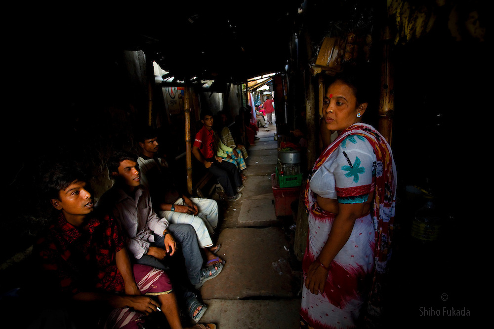 """Aging sex worker Josna, 60, tries to get a cutomer at brothel in Faridpur, Bangladesh. As she ages, she finds difficult to get a customer. """"I grab and pull a customer into my room and just reveal myself."""" she says."""
