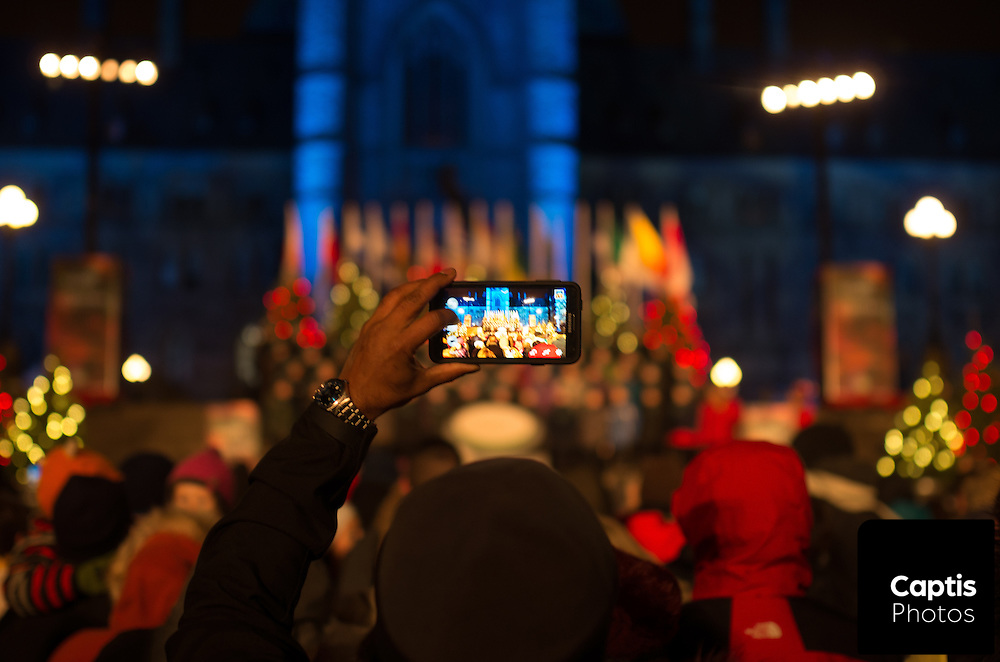 A man takes a photo of the main stage during the opening ceremony for Holiday lights on Parliament Hill. December 3, 2014.