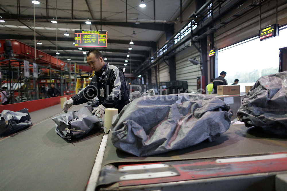 Workers sort and move packages at a SF Express sorting facility near the airport in Hangzhou , China on 11 November 2013. Express courrier services are facing logistical shortages as Chinese consumers increasingly shop online, with the success of an online retail often depend on the speed of its deliveries.