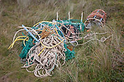 A pile of assorted ropes and fibrous cord and fishing pots await removal from the coastal landscape, having been collected by volunteers from a beach on Holy Island, on 27th September 2017, on Lindisfarne Island, Northumberland, England. The amount of rubbish found dumped on UK beaches rose by a third last year, according to a new report. More than 8,000 plastic bottles were collected by the Marine Conservation Society's annual beach clean-up at seaside locations from Orkney to the Channel Islands on one weekend in September 2016. The Holy Island of Lindisfarne, also known simply as Holy Island, is an island off the northeast coast of England. Holy Island has a recorded history from the 6th century AD; it was an important centre of Celtic and Anglo-saxon Christianity. After the Viking invasions and the Norman conquest of England, a priory was reestablished.