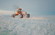 Alaska, North Slope. The blade works ice road building material to construct an ice bridge