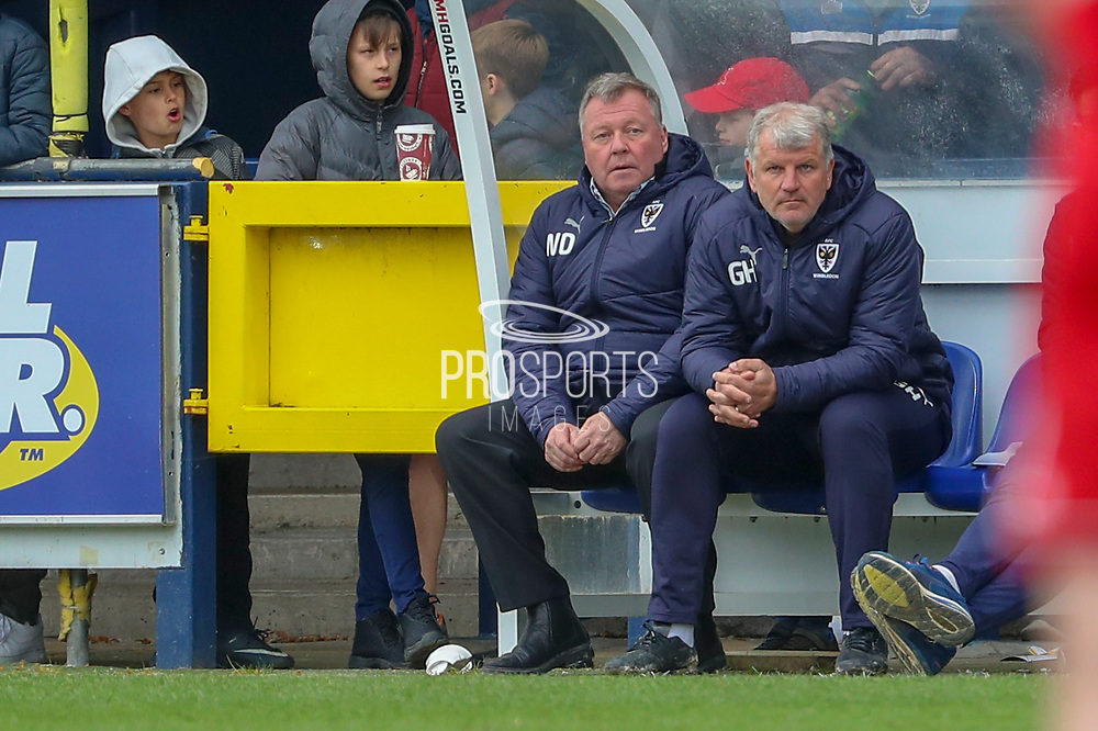 AFC Wimbledon manager Wally Downes and AFC Wimbledon first team coach Glyn Hodges looking onto the pitch during the EFL Sky Bet League 1 match between AFC Wimbledon and Accrington Stanley at the Cherry Red Records Stadium, Kingston, England on 6 April 2019.