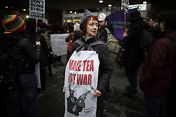 """© Licensed to London News Pictures . 05/12/2015 . Manchester , UK . A woman wearing a tea towel with MAKE TEA NOT WAR printed on it . Approximately one hundred anti-war protesters march through central Manchester against Parliament's decision to vote in favour of bombing against """" ISIS """" , in Syria . Photo credit : Joel Goodman/LNP"""