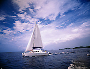 A sailboat cruises along through blue carribean waters on a sunny day