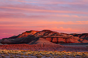 Altocumulus clouds, turned red by the setting sun, streak over badlands near the Blue Mesa in Petrified Forest National Park, Arizona. Badlands are a type of dry terrain where clay or soft sedimentary rock have been heavily eroded by rain and wind and where vegetation is scarce.