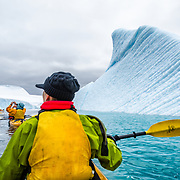 A group of kayakers paddle by large carved icebergs at Melchior Island in Antarctica.