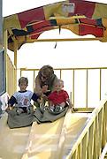 Mom age 30 instructing sons on giant Minnesota State Fair slide age 5 and 3.  St Paul Minnesota USA