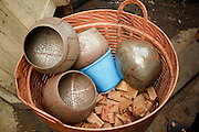 "Mar. 21, 2009 -- BANGKOK, THAILAND:  Monk's Bowls wait to be finished in a workshop in the Monk's Bowl Village. The Monk's Bowl Village on Soi Ban Baat in Bangkok is the only surviving one of what were originally three artisan's communities established by Thai King Rama I for the purpose of handcrafting ""baat"" the ceremonial bowls used by monks as they collect their morning alms. Most monks now use cheaper factory made bowls and the old tradition is dying out. Only six or seven families on Soi Ban Baat still make the bowls by hand. Most of the bowls are now sold to tourists who find their way to hidden alleys in old Bangkok. The small family workshops are only a part of the ""Monk's Bowl Village."" It is also a thriving residential community of narrow alleyways and sidewalks.     Photo by Jack Kurtz"