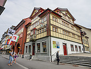 In Appenzell village, the red Rathaus (built 1560-83) houses the city hall, Appenzell Museum (in attached yellow building), tourist office and library, on Hauptgasse (Main Street), in Switzerland, Europe. The Rathaus facade mural was painted by August Schmid from Diessenhofen (1928). Appenzell Museum shows a cross section of the Swiss Canton's history and culture (1400s flags and banners, embroidery, folk art, and even historic torture instruments). Appenzell village is in Appenzell Innerrhoden, Switzerland's most traditional and smallest-population canton (second smallest by area). This image was stitched from multiple overlapping photos.