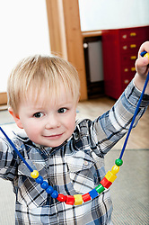 Proud little boy showing selfmade wooden perl necklace