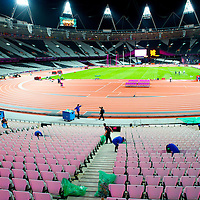 Janitorial staff clean the Olympic Stadium at the completion of track and field events long after the crowds have all departed the venue during the 2012 London Summer Olympics.