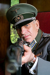 A Reenactor portraying a German Army (heer) Medical Captain (Hauptmann) aims his MP38 on the East Lancashire Railway 1940's Weekend. He is wearing an officer's Schirmmütze<br />  <br /> <br />  Copyright Paul David Drabble<br />  www.pauldaviddrabble.co.uk