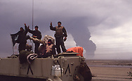 Saudi Troops standing on their broken personnel carrier wave as other troops head to Kuwait City on the three day of the Gulf War.<br /><br />Photograph ny Dennis Brack. bb78