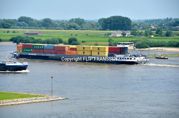 Nederland, Varik, 9-6-2018 Een binnenvaartschip vaart over de Waal beladen met containers richting Duitsland . In dit deel van de Waal zijn de kribben verlaagd of vervangen door langsliggende dammen om de waterafvoer te verbeteren . Het fietsveer, voetgangerspontje, vaart aan de overkant . De Waal is het Nederlandse deel van de Rijn en de belangrijkste vaarroute van en naar Rotterdam en Duitsland . Foto: Flip Franssen