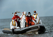 U2 Band with manager Paul McGuinness on a boat trip to a radioactive Sellafield beach dressed in anti radiation suits for a 1992 Greenpeace Demo.