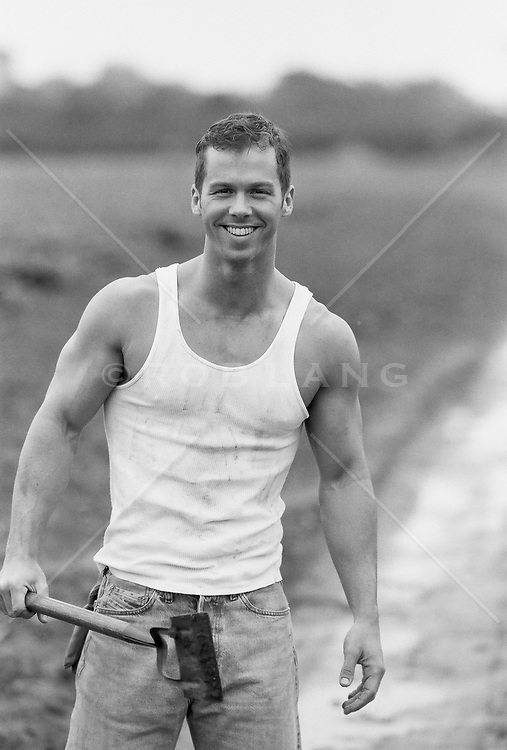 muscular man outdoors with a garden tool