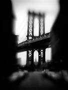 A shadowy image of a side-street and the Manhattan Bridge in New York City. The Manhattan Bridge is one of the most heavily traveled East River crossings in New York and is 6,855 feet in total length.