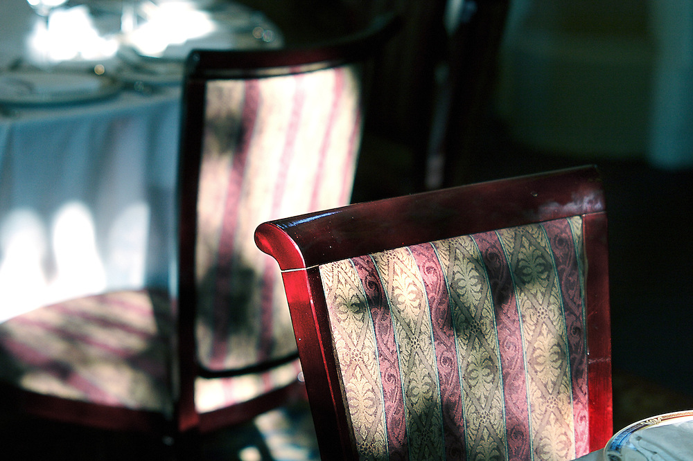 Shadow and sunlight decorates high-backed chairs in reception venue.