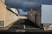 Rainclouds over coloured houses on street, Kilkee, Co. Clare, Ireland