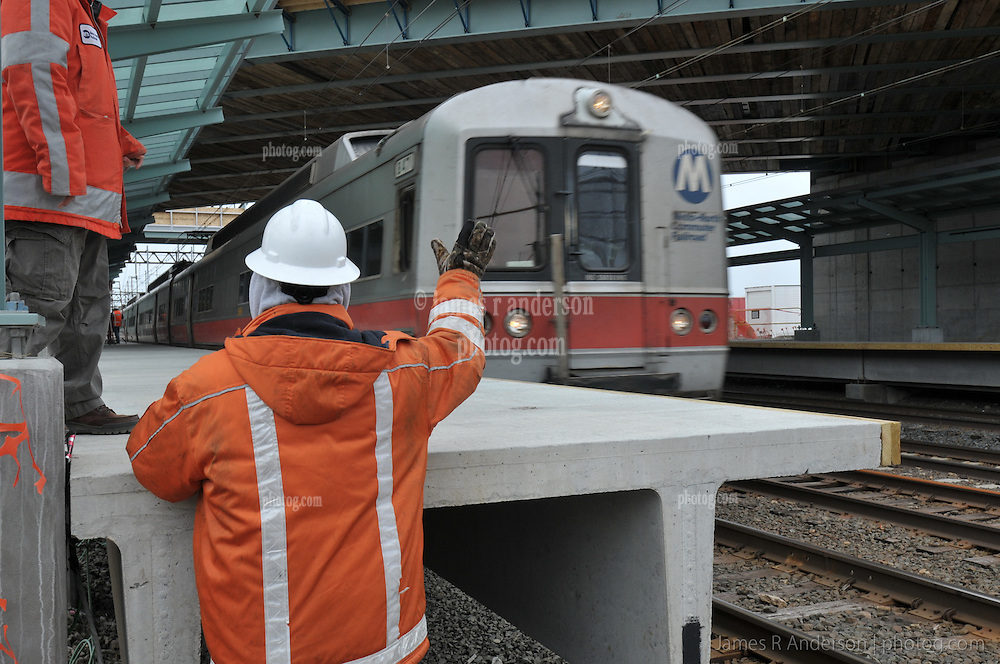 Flagman waves to passing trainset Engineer. Metro-North Commuter Railroad at the under construction Rail Station at Fairfield Metro, CT