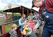 Randy Williams, President of the The Chelatchie Prairie Railroad Association hands out flowers for Mother's day in Yacolt, Sunday May 11, 2014.   The 2014 season kicks off this weekend with a 12-mile round trip ride through north Clark County. Natalie Behring/for the Columbian)