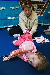 Carer putting splints on disabled child,