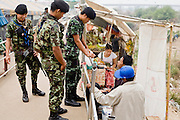"""27 FEBRUARY 2008 -- MAE SOT, TAK, THAILAND: Thai soldiers on the Thai side of the border talk to Burmese cigarette smugglers on the Burmese side of the border along the Thai - Myanmar (Burma) border in Mae Sot, Thailand. Thai authority ends at the metal railing separating the men and Burmese smugglers line up along the rail to sell cigarettes and liquor to people on the Thai side of the rail. There are millions of Burmese migrant workers and refugees living in Thailand. Many live in refugee camps along the Thai-Burma (Myanmar) border, but most live in Thailand as illegal immigrants. They don't have papers and can not live, work or travel in Thailand but they do so """"under the radar"""" by either avoiding Thai officials or paying bribes to stay in the country. Most have fled political persecution in Burma but many are simply in search of a better life and greater economic opportunity.  Photo by Jack Kurtz"""