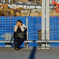 A man holding his head in his hands after a days work on Wall Street waits for his ferry to arrive at Pier 11 Wall Street.