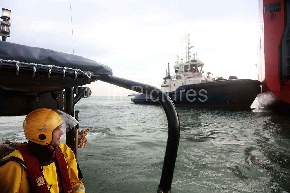 A tug boat pushes the cargo ship into place near Sheerness harbour watched by a Greenpeace crew September 21st 2017, Thames Estuary, Kent, United Kingdom. Greenpeace volunteers in kayaks, speed boats and climbers on the jetty prevent the 23,498-tonne cargo ship Elbe Highway from docking at Sheerness in Kent.  The cargo ship is bringing Volkswagen diesel cars into the UK and the Greenpeace action is to prevent this from happening and to make VW ditch diesel. Two climbers board the ship and hang a banner on the roll-on roll-off part of the ship preventing any cars from being off-loaded. The action is part of a long running Greenpeace campaign to curb diesel emmissions and air pollution broght on by diesel cars.
