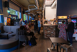 © Licensed to London News Pictures. 26/08/2021. London, UK. Visitors play retro arcade video games at the opening of Four Quarters arcade bar in Elephant and Castle. Thius is the groups third arcade bar opening an featyures many retro arcade games. Photo credit: Ray Tang/LNP