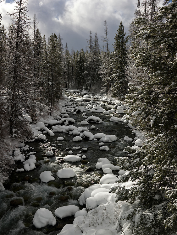 Snow covered boulders in Little Redfish Outlet stream on a cold winters morning with breaking storm in the Sawtooth Mountains of Central Idaho. Licensing and Open Editions Prints.